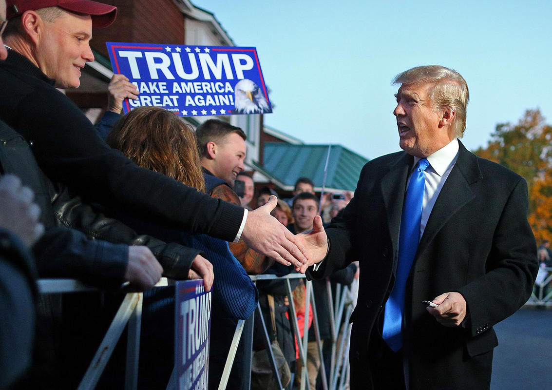 Donald Trump shakes hands as he arrives to address a crowd. From Boston Herald (c) 2015 Staff Photo by Nancy Lane.